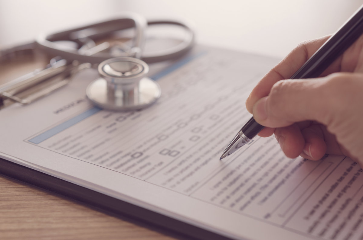 closeup pen in hand's doctor notes data on medical document.